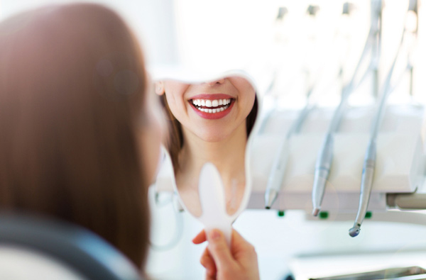 Woman looking at her smile in a mirror at Oak Dental Care in Port Charlotte, FL